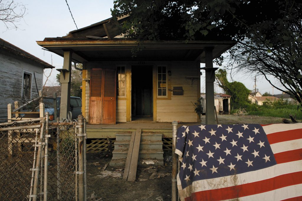 photo of house with flag over fence